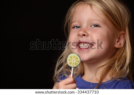 Portrait of a young girl with lollipop on black background - stock photo