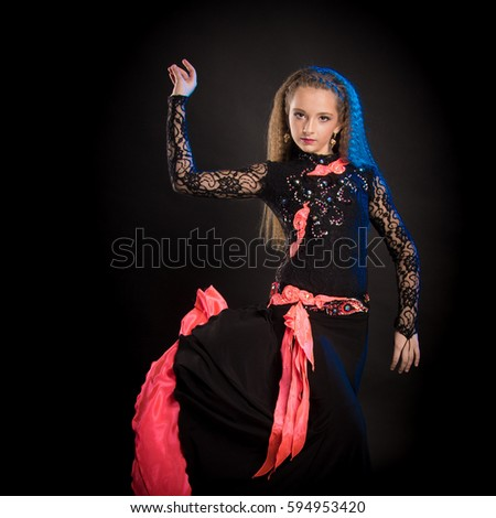 Portrait of a young girl with long hair in a black lace suit of a dancer with a bright red shawl posing on a black background in a scenic blue light