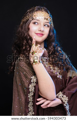 portrait of a young girl with long hair in oriental dancer costume Khaleej posing and dancing on a black background in the scenic blue light