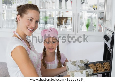 Portrait of a young girl with mother removing cookies from the oven in the kitchen - stock photo