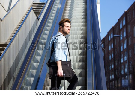Portrait of a young guy with bags walking up escalator - stock photo