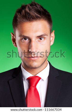 Portrait of a young handsome business man, on green background - stock photo