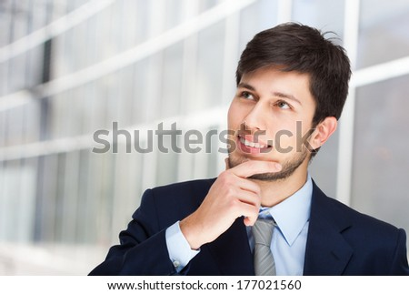 Portrait of a young handsome businessman looking up - stock photo