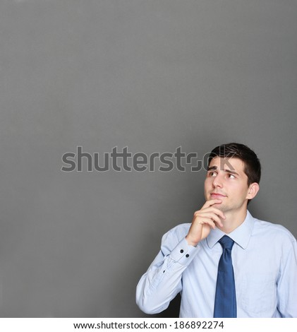 portrait of a young handsome businessman thinking - stock photo