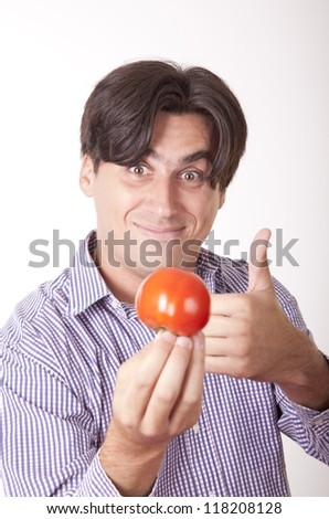 Portrait of a young handsome casual man offering a tomato.