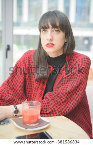 Portrait of a young handsome caucasian brown hair woman seated on a bar posing looking in camera - freshness, youth, carefree, concept - stock photo