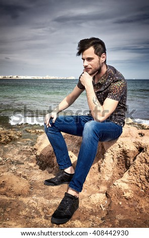 Portrait of a young handsome guy sitting on the rocks near a beach, hand under chin. - stock photo