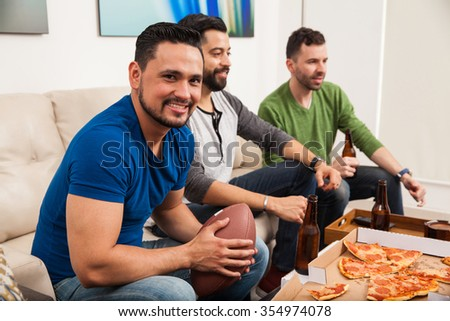 Portrait of a young Handsome Hispanic man watching an american football game with his friends and eating some pizza - stock photo