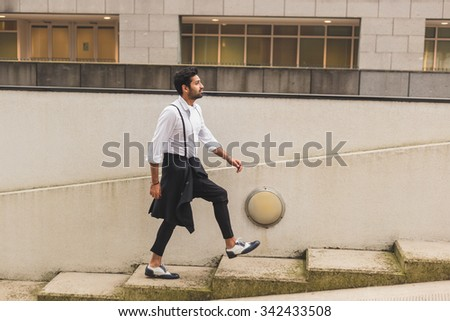 Portrait of a young handsome Indian man posing in an urban context - stock photo