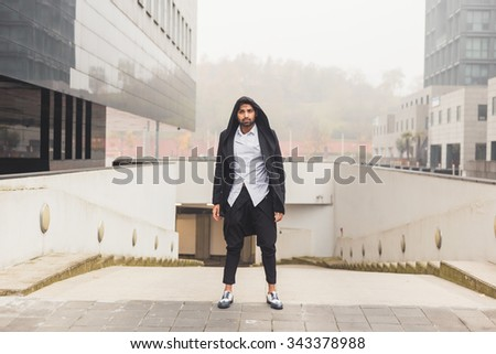 Portrait of a young handsome Indian man posing in an urban context