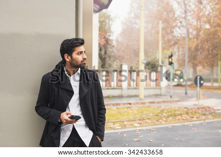Portrait of a young handsome Indian man texting in an urban context - stock photo