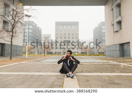 Portrait of a young handsome Indian man with headphones listening to music in an urban context