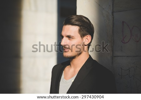 Portrait of a young handsome italian boy posing leaning on a wall in the city center - stock photo