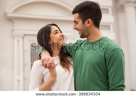 Portrait of a young handsome man and his beautiful girlfriend hanging out in the city - stock photo