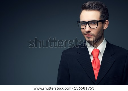 Portrait of a young handsome man (businessman) in black suit with trendy pink tie, stylish glasses smiling and looking at camera. Copy-space. Studio shot