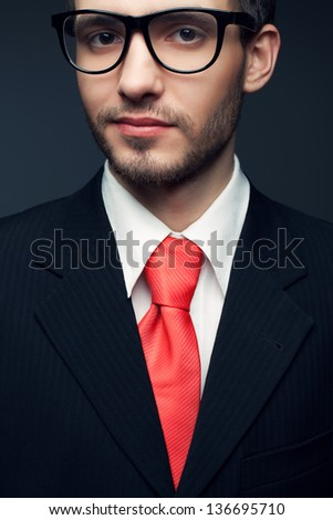 Portrait of a young handsome man (businessman) in black suit with trendy pink tie, stylish glasses smiling and looking at camera. Close up. Studio shot
