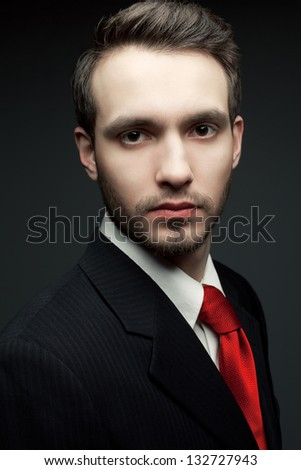 Portrait of a young handsome man (businessman) in black suit with trendy red tie. Studio shot