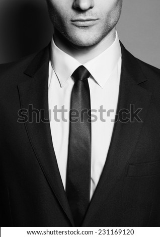 Portrait of a young handsome man (businessman) in classic suit, white shirt with trendy blue tie. Close up. Studio shot - stock photo