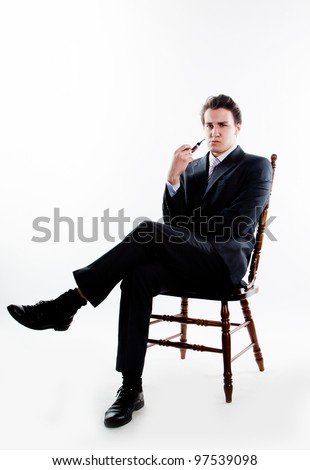 Portrait of a young handsome man in a dark suit with a strict smoking a pipe in his hand