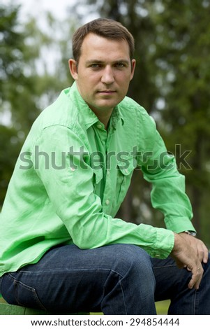 Portrait of a young handsome man in a green shirt on the background of summer park - stock photo