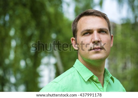Portrait of a young handsome man in a green shirt on the background of summer park
