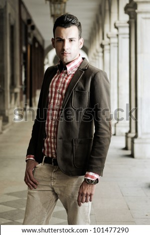 Portrait of a young handsome man, model of fashion, wearing jacket and shirt in urban background - stock photo
