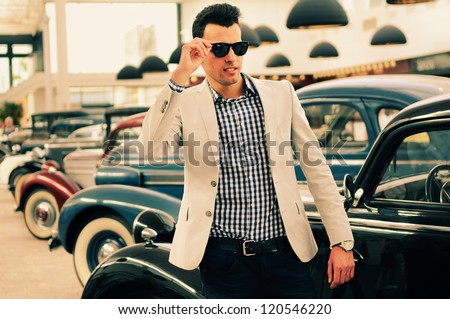 Portrait of a young handsome man, model of fashion, wearing jacket and shirt with old cars