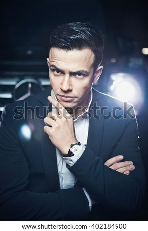 Portrait of a young handsome man, model of fashion, wearing jacket and shirt with old cars - stock photo