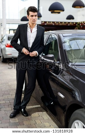 Portrait of a young handsome man, model of fashion, wearing suit and with luxury car - stock photo