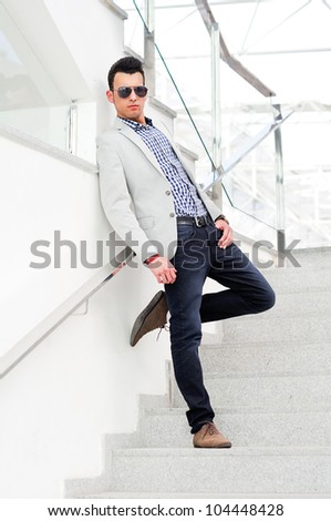 Portrait of a young handsome man, model of fashion, wearing tinted sunglasses - stock photo