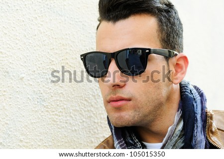 Portrait of a young handsome man, model of fashion, wearing tinted sunglasses in urban background - stock photo