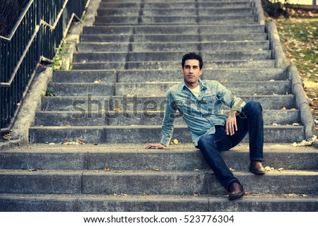 Portrait of a young handsome man, model of fashion, with formal hairstyle sitting in urban stairs, wearing casual clothes. Blue eyes guy in urban background.