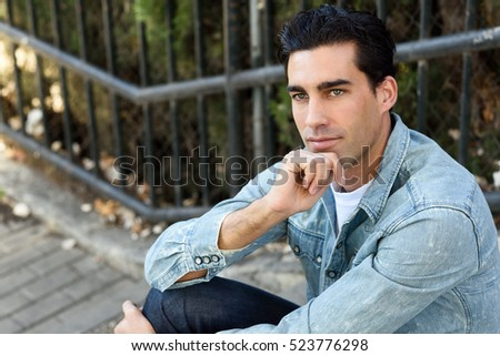 Portrait of a young handsome man, model of fashion, with formal hairstyle thinking in urban stairs, wearing casual clothes. Blue eyes guy in urban background.