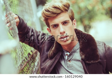 Portrait of a young handsome man, model of fashion, with modern hairstyle in urban background wearing aviator leather jacket. Blonde hair - stock photo