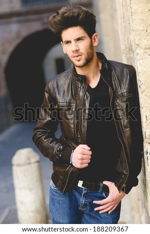 Portrait of a young handsome man, model of fashion, with modern hairstyle in urban background wearing leather jacket