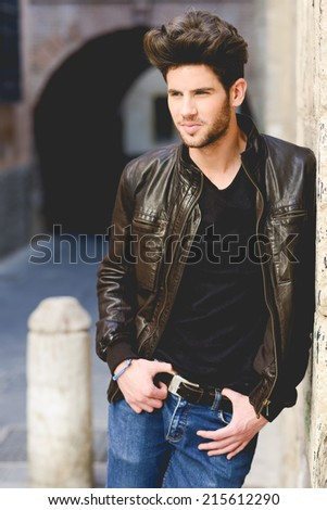 Portrait of a young handsome man, model of fashion, with modern hairstyle in urban background wearing blue jeans and leather jacket - stock photo