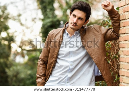 Portrait of a young handsome man, model of fashion, with modern hairstyle in urban background, wearing casual clothes. - stock photo