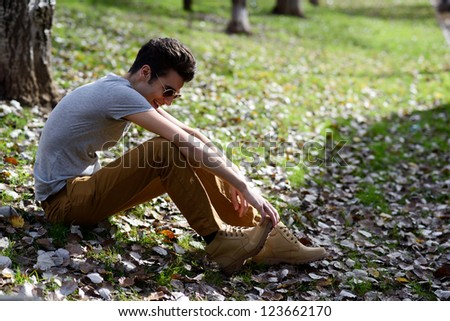 Portrait of a young handsome man, model of fashion, with toupee laughing in the park - stock photo
