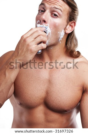Portrait of a young handsome man shaving as part of his morning routine.