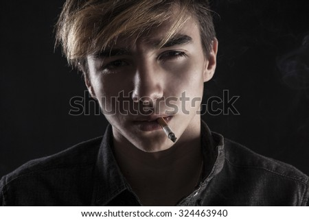 portrait of a young handsome man smoking a cigarette on black background