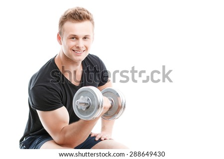 Portrait of a young handsome man wearing black t-shirt sitting smiling and holding a silver dumbbell in his hand showing his muscled biceps during training, isolated on white background - stock photo