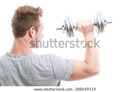 Portrait of a young handsome man wearing grey t-shirt standing and holding a silver dumbbell in his hand showing his muscled biceps during training, isolated on white background view from the back - stock photo
