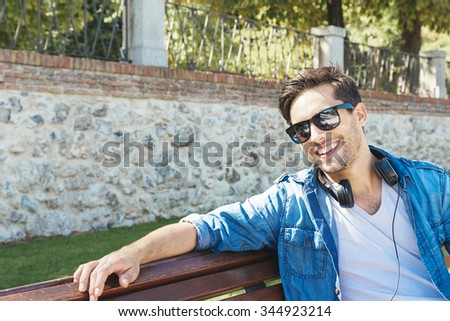 Portrait of a young handsome man with headphones in nature background - stock photo