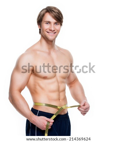 Portrait of a young handsome man with muscular torso uses measuring tape on a white background. - stock photo