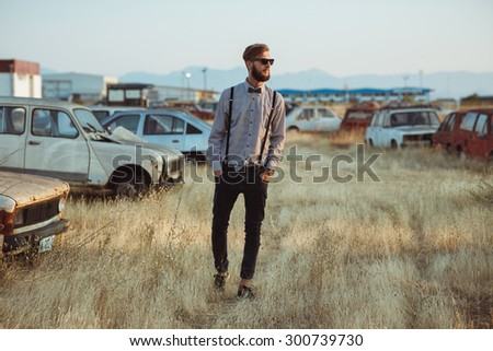 Portrait of a young handsome stylish man, wearing shirt and bow-tie on the field of old cars - stock photo