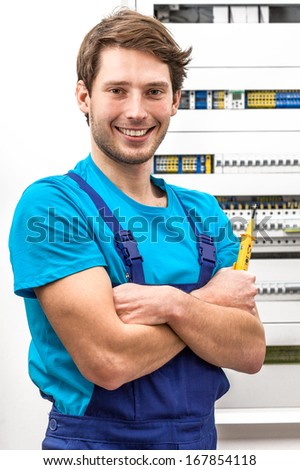Portrait of a young handyman with multimeter - stock photo