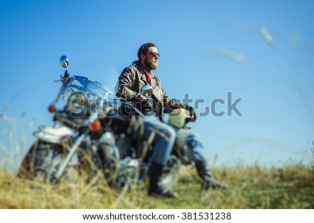 Portrait of a young happy biker with beard sitting on his cruiser motorcycle. Man is wearing leather jacket and blue jeans. Low point of view. Tilt shift lens blur effect - stock photo