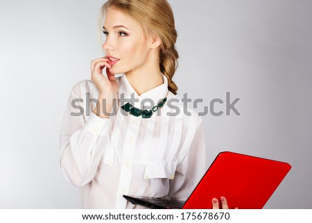 Portrait of a young happy business woman with a laptop over white background