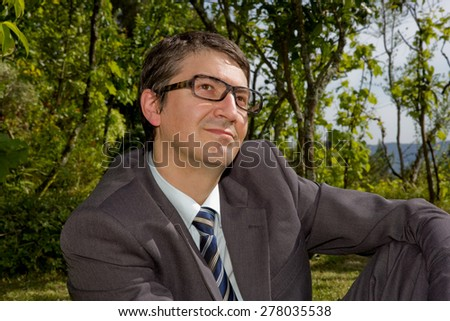 portrait of a young happy businessman with glasses, outdoors - stock photo