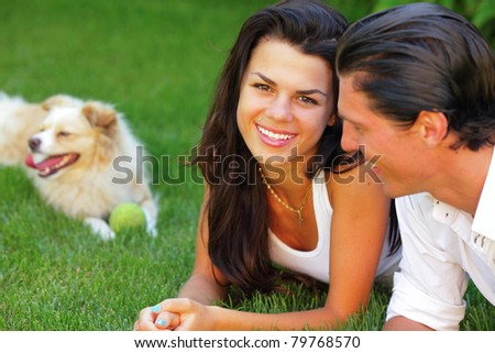 Portrait of a young happy couple with a playful dog